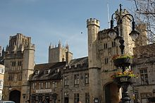 Ornate stone buildings. 2 archways beneath towers. In the foreground is a lamp stand with flowers.