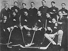 Fourteen men pose around a silver trophy. Several are wearing identical sweaters with a buffalo logo over the left breast and are holding hockey sticks.