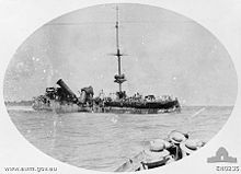 A badly damaged ship sits in the water, while in the foreground sailors in another vessel watch on