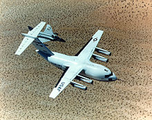 Top view of cargo aircraft in-flight, trailed by a fighter chase plane. Under each un-swept wing are two engines suspended forward ahead the leading edge.