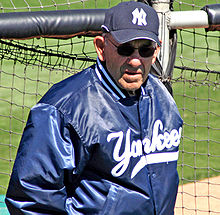 A man wearing sunglasses, along with a navy blue jacket and baseball cap that have white lettering.