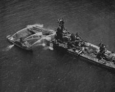 Aerial photo of a fireboat hosing down the stern of a battleship.
