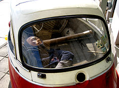 Tiny red and white bubble car, viewed from the rear, with a dummy in the rear representing a person being concealed in the car.