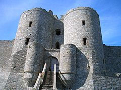 Two cylindrical stone towers flanking a gateway, and behind them two larger cylindrical towers. A path leads up to the gateway and curtain walls are attached to the towers.