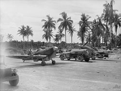 Black-and-white photo of two single-engined monoplane aircraft and a fuel tanker on a dirt clearing. Tropical palms are visible in the background.