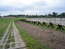 Strip of bare ploughed earth flanked by a concrete road on one side and a row of barricades and a fence on the other side, with buildings visible in the far background.