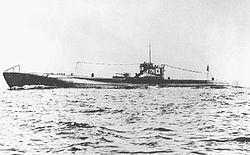 Large submarine running on the surface of the sea with a prominent deck gun and with radio mast raised