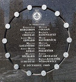 "commemorative plaque in polished stone, deeply engraved with in circle with 14 small silver disks distributed around the circle. Inside, and under the university's logo and the legend ""In Memoriam"" are the names of the 14 victims and the date of the massacre"