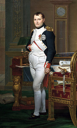 Full length portrait of Napoleon in his forties, in high-ranking white and dark blue military dress uniform. He stands amid rich 18th century furniture laden with papers, and gazes at the viewer. His hair is Brutus style, cropped close but with a short fringe in front, and his right hand is tucked in his waistcoat.