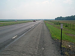 An expressway, seen from the shoulder of its righthand lanes, continues straight ahead to the center of the image. Either side is fenced off; the surrounding area is mostly marsh with a wooded area visible at right center