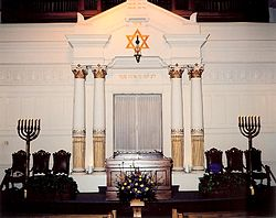 A white wall with an inset Torah ark at its center faces the viewer. Atop the ark is gold-colored Hebrew writing, and atop that a hanging lamp suspended from the center of a gold-colored Star of David. On each side of the ark are tall white columns, and beside them three ornate dark chairs and large seven branched menorahs. In front of the ark is a wooden pulpit.