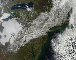 A satellite image of the northeastern United State. A swath of snow covers the ground from the Appalachians in western Virginia through Pennsylvania, northern and central New Jersey, the New York City metropolitan area and Hudson Valley into New England. There are patches of cloud on either side.