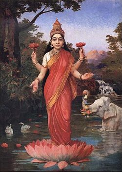 A woman wearing red and gold clothes,standing in a lotus that is on water, has four arms, and is holding a lotus in her back hands.