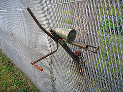 Horn-shaped device mounted on the side of a metal fence, with trigger wires attached to it and running parallel to the fence into the foreground and background.