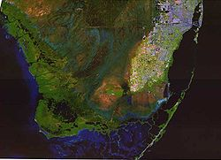 A color satellite image of the southern Everglades, Florida Bay, Atlantic Ocean, and Gulf of Mexico; the Everglades are green with large sections of blue water, with some brown raised areas and the southernmost tip of the South Florida Metropolitan Area in white