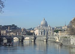A view of Rome on a sunny afternoon looking along the river. A bridge crosses the river and beyond it is a hill on which the grey dome of St Peter's rises above ancient buildings and dark pine trees.