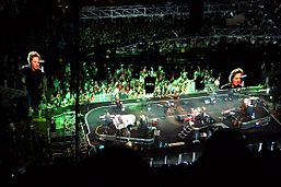 A large arena stage is seen from above with about ten musicians, including a drummer on a stand, as video screens show the singer and green lighting shines on the stage and audience