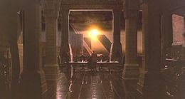 A screen-shot from the film depicts a large room as we look between two rows of pillars. At the far end of room there is a massive window that dwarfs a man in front of it. The man is facing away from us looking out of the window, through which the sun can be seen.