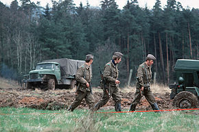 Three uniformed men, armed with assault rifles, walking in a column through a grassy landscape with dense trees in the background. A canvas-sided truck is visible in the left background and part of another vehicle is seen on the right in a stretch of ploughed-up ground.