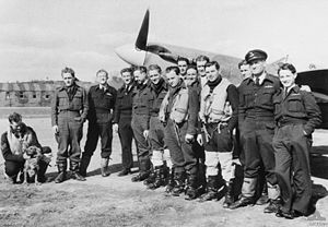 Thirteen men wearing military uniform standing close together in front of a single propeller monoplane. A fourteenth man wearing military uniform is crouching and patting a dog to the left of the group.