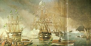 A painting depicting tall-masted sailing ships dressed with flags in the background, some of which are firing cannon salutes, and a large covered launch flying a huge green flag being rowed towards the shore, followed by a crowd of smaller craft