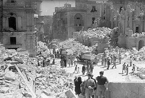 Service personnel and civilians clear up debris on a heavily bomb-damaged street in Valletta, Malta on 1 May 1942
