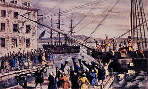Two ships in a harbor, one in the distance. Onboard, men stripped to the waist and wearing feathers in their hair throw crates of tea overboard. A large crowd, mostly men, stands on the dock, waving hats and cheering. A few people wave their hats from windows in a nearby building.