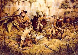 A painting of three Marines fighting in a jungle. There is a brick wall in the background with a lot of plants and trees. An enemy fighter is in the foreground and appears to be dead.