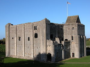 A square building of grey stone with narrow vertical slits on the first floor, and wider windows on the second. The top of the castle looks decayed and there is no roof, except over a tower attached to the keep.