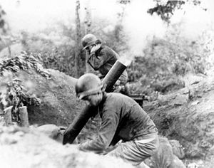 Two men in uniform brace as a mortar tube launches a rocket in the middle of a jungle
