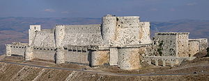 A stone castle with two high curtain walls, one within the other. They are crenelated and studded with projecting towers, both rectangular and rounded. The castle is on a promontory high above the surrounding landscape.