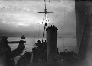 View from the cruiser HMS Sheffield as she sails on convoy duty through the waters of the Arctic Ocean. In the background are merchant ships of the convoy. The image was taken during the twilight of the arctic winter—the short time each day that the sun is seen during winter near the pole. In the foreground is the silhouette of a lookout using a telescope.