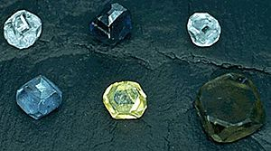 Six non-faceted diamond crystals of 2–3 mm size; the diamond colors are yellow, green-yellow, green-blue, light-blue, light-blue and dark blue