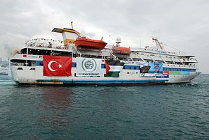 Photo of white cruiser yacht, adorned with banners of Turkey and Palestine