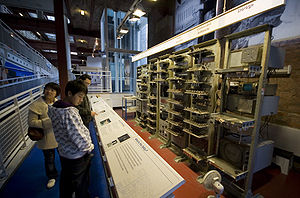 A series of seven tall metal racks filled with electronic equipment standing in front of a brick wall. Signs above each rack describe the functions carried out by the electronics they contain. Three visitors read from information stands to the left of the image.