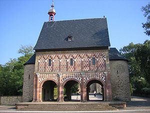 The 9th-century Torhalle (gatehouse) is a unique survival of the Carolingian era. It curiously combines some elements of the Roman triumphal arch (arch-shaped passageways, half-columns) with the vernacular Teutonic heritage (baseless triangles of the blind arcade, polychromatic masonry).