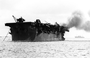 Photograph of badly damaged aircraft carrier, afloat with smoke coming from deck.