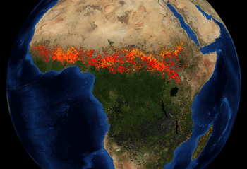 An artificially coloured satellite view of Africa, with red and yellow markers where fires have been detected. A wide red band of markers runs east-west, just south of the Sahara Desert.
