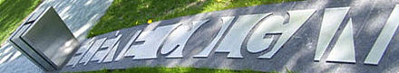 a waist high grey box is carved with a large H; the rest of Hélène Colgan's name is spelled out in large raised lettering on the ground of the park