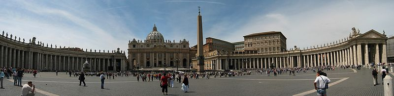 Panorama showing the facade of St Peter's at the centre with the arms of Berninis colonnade sweeping out on either side. It is midday and tourists are walking and taking photographs.