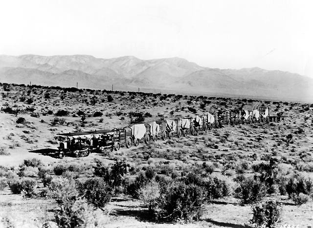 Two Holt 45 gas crawler tractors team up to pull a long wagon train in ...